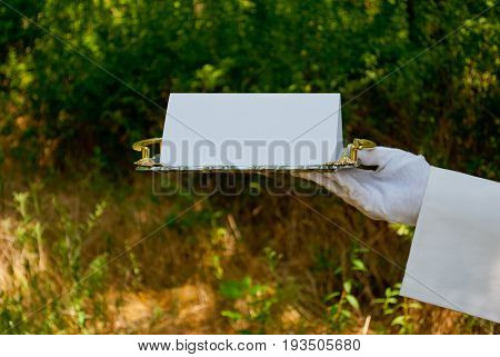 A waiter's hand in a white glove and with a white napkin holds a metal tray of silvery rectangular metal with a white sign on a blurred background of nature green bushes and trees