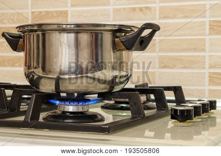 Metal cooking pot standing on kitchen stove with flame.