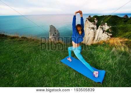 Athletic young woman in sportswear doing fitness exercise standing on the top of the cliff against beautiful waterscape