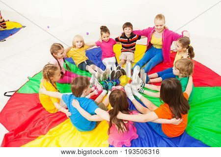 Big group of happy children sitting in a circle with nursery teacher, hugging and playing games