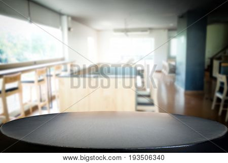 Selected focus empty black wooden table and Coffee shop or cafe blur background with bokeh image. for your photomontage or product display.