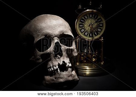Human skull with vintage clock close up on black background.