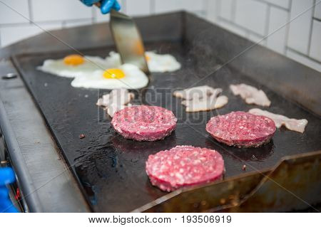 Chief Cook Preparing Fresh Burger In The Kitchen. Burger Restaurant Menu Cooking Process. The Chief