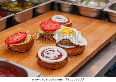 Chief Preparing Fresh Burger In The Kitchen.burger Restaurant Menu Cooking Process. Burger Ingridien