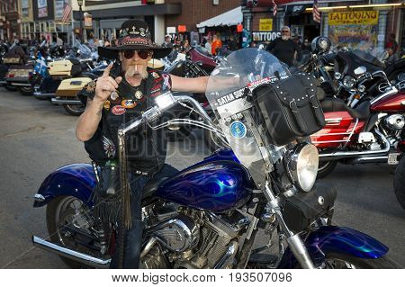 Sturgis South Dakota - August 9 2014: Rider in the main street of the city of Sturgis in South Dakota USA during the annual Sturgis Motorcycle Rally