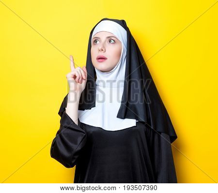 Portrait of young nun on yellow background