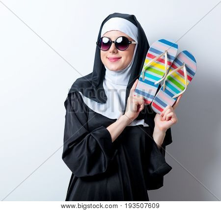 Young Smiling Nun In Sunglasses With Flip Flops