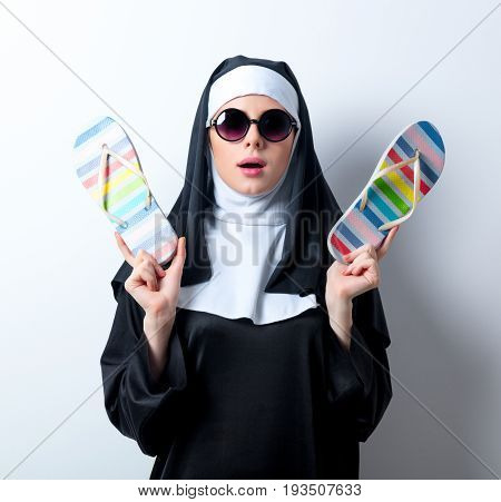 Young Surprised Nun In Sunglasses With Flip Flops
