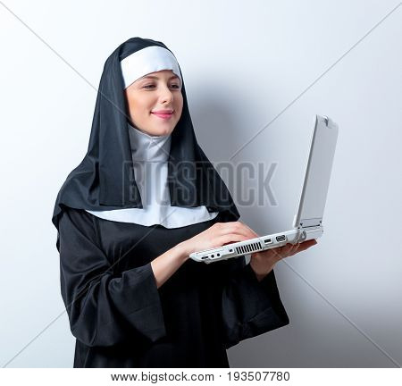 Young Smiling Nun With Laptop Computer