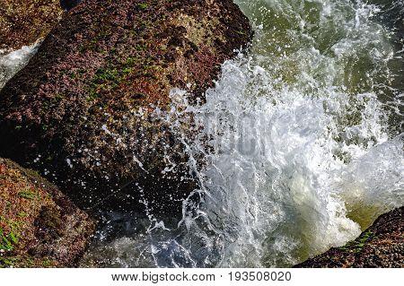 Sea water splash over beach stones with moss