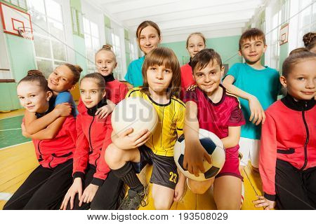 Group of happy 11-12 years old boys and girls wearing sportswear, sitting together in school gymnasium