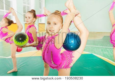 Portrait of 11 years old girl performing rhythmic gymnastics elements with ball