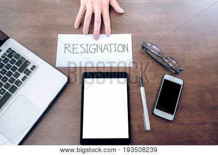 Image of businessman hand sending a resignation letter to executive boss with glasses pen and laptop on a wooden table Change of job unemployment resign concept.