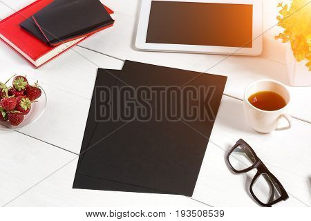 Stylish minimalistic workplace with tablet and notebook and glasses in flat lay style. White background. Top view. Copy space. sun flare