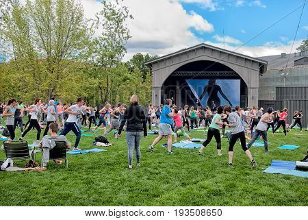 SAINT - PETERSBURG, RUSSIA - JULY 2, 2017: People doing collective fitness training on the lawn of The New Holland Island. It is an artificial island in the center of the city. Was created in 1719.