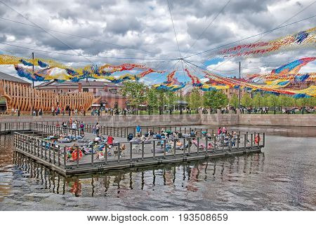 SAINT - PETERSBURG, RUSSIA - JULY 2, 2017: People rest on the pontoon of New Holland Island. Over the people is a giant Firebird Descent Art Installation by Patrick Shearn artist of Poetic Kinetics
