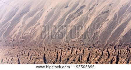 Desert with brown rugged terrain and sand barchan dunes from airplane flight on natural background geology and geographic concept
