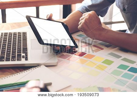 Color samples color swatch samples Draw architecture Graphic designer selecting on colour chart pens at workplace Working with laptop and tablet on wooden desk.