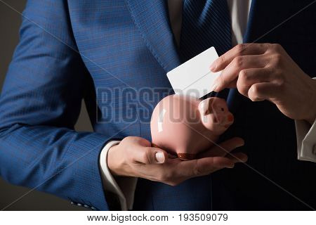 Hands Putting Blank Business Card In Piggy Bank