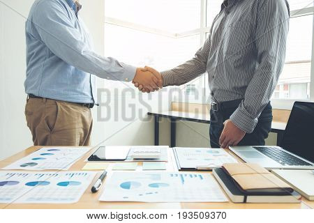 Two business men shaking hands during a meeting to sign agreement and become a business partner enterprises companies confident success dealing contract between their firms.
