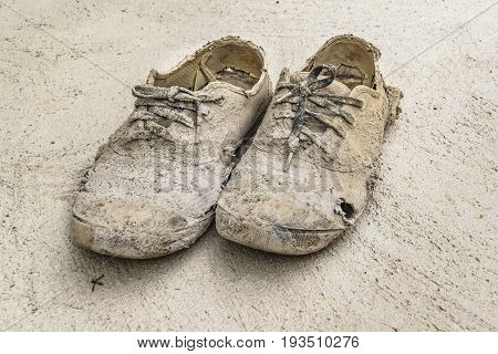 Used damaged construction worker shoes at ground