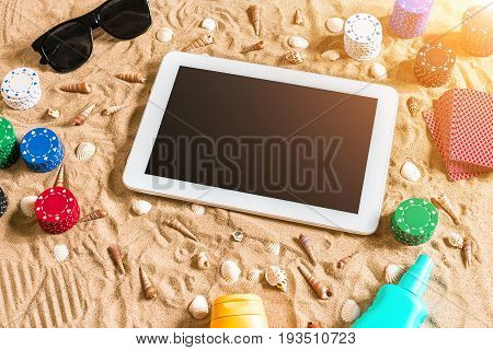 Gambling on vacation concept - white sand with seashells , colored poker chips and cards. Top view. Copy space. Summer. Sun flare