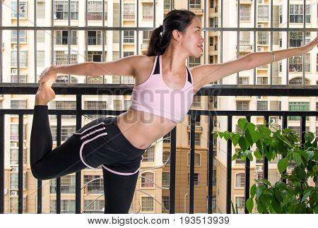 Girl Doing Standing Bow Yoga Pose Variation At Home
