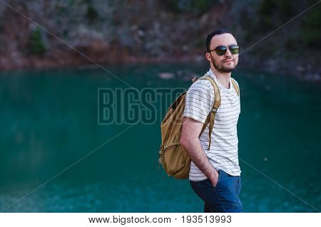 Handsome bearded man, with hands in his pockets, looking away standing near lake. Young guy wearing sunglasses and a fashionable clothes, discover world, stylish cool mans portrait.