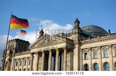 BERLIN, GERMANY - MAY 12, 2017: German flag waving at Bundestag building in a sunny day with blue sky.