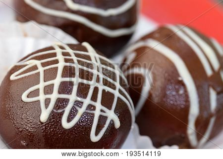 Close view on the three chocolate Praline with white lines decoration with transparent white/red plate background
