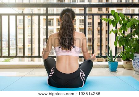 Girl Meditating At The Balcony On A Yoga Mat