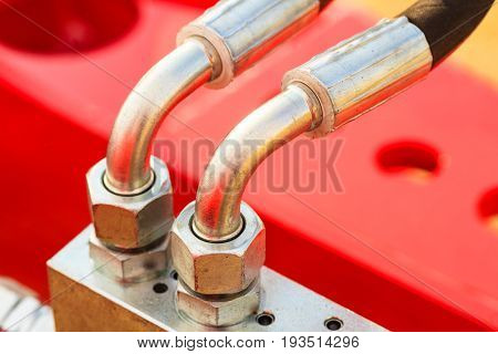 Industrial detailed pneumatic hydraulic machinery concept. Pump made of steel on red machine closeup.