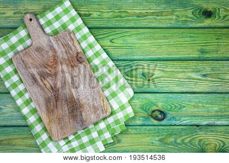 Cutting board over green checkered tablecloths on the table, top view