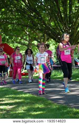 SOUTHAMPTON UK - July 2 2017: Race for Life women run and walk to raise money for Cancer Research charity in Southampton UK. Girl running with her mother dressed up in rainbow tutu; gloves and leg warmers.