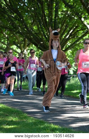 SOUTHAMPTON UK - July 2 2017: Race for Life women and children run and walk to raise money for Cancer Research charity in Southampton UK. Boy dressed as Scooby Doo dog running race.