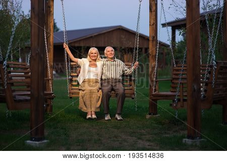 Senior couple on porch swing. Man and woman outdoor, evening.