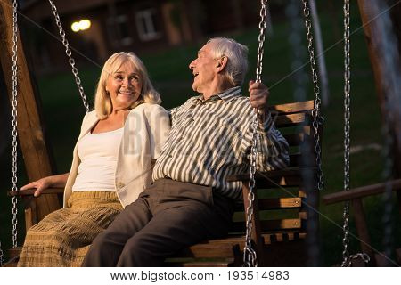 Couple on porch swing, evening. Senior man and woman laughing.