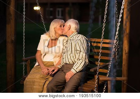 Couple kissing on porch swing. Senior people outdoors, evening.