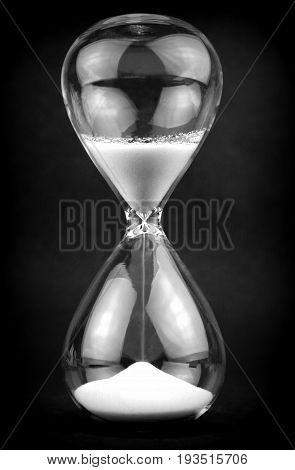 Hourglass on black backgrund close up image