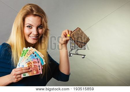 Happy woman holding shopping basket with bread holding money enjoying low prices.