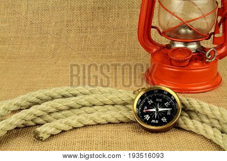 Old compass oil lamp and rope on burlap