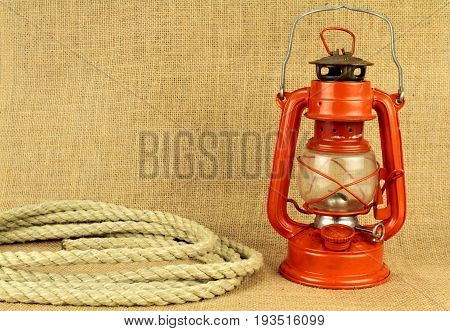 Red oil lamp and rope on burlap