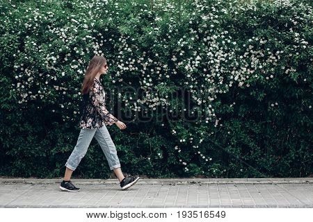 Hipster Woman In Sunglasses Walking On Background Of Blooming Bush With White Flowers Of Spirea. Boh