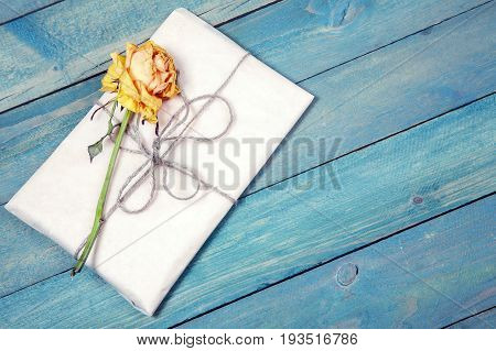 One dried yellow rose with blank photo frame on old blue wooden background