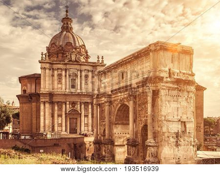 The Roman Forum Rome, Italy. Triumphal arch of Septimius Severus and medieval church of Santi Luca e Martina. Roman Forum is one of the main tourist attractions of Rome.