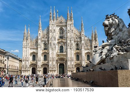 MILAN, ITALY - MAY 16, 2017: Tourists visit the Milan Cathedral (Duomo di Milano) on the Piazza del Duomo. Milan Duomo is the largest church in Italy.