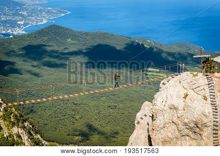 CRIMEA, RUSSIA - MAY 19, 2016: Tourist walking on rope bridge on the Mount Ai-Petri. Ai-Petri is one of the highest mountains in Crimea and tourist attraction.