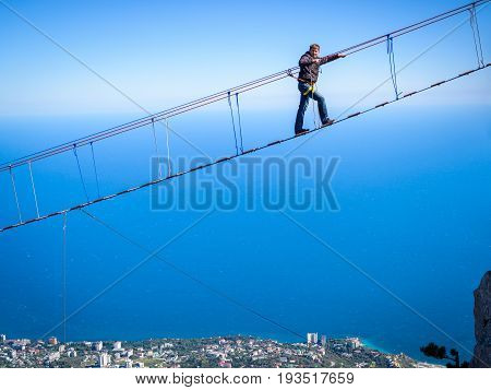 CRIMEA, RUSSIA - MAY 19, 2016: Tourist walking on a rope bridge on the Mount Ai-Petri. It is one of the highest mountains in Crimea and tourist attraction.