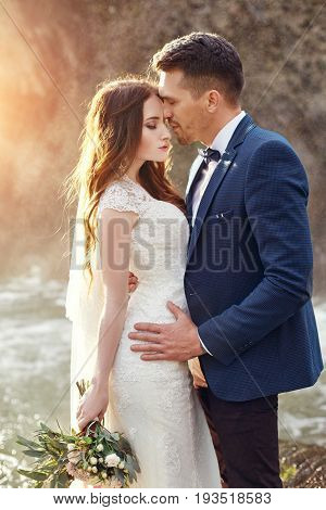 Couple hugging at sunset lovers couple kissing in sunset. Wedding ceremony outdoors. Beautiful bride and groom with bouquet of flowers. White wedding dress for bride. Love wedding couple hug. Blurred