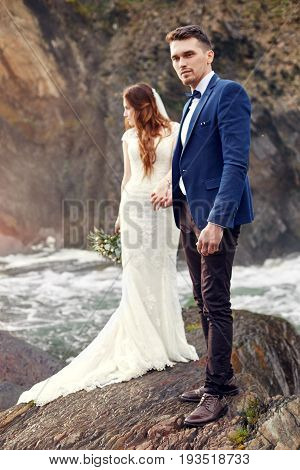 Beautiful couple in love kissing while standing on rocks by sea. Wedding couple at sunset and surf love and tender feelings. Loving couple resting. Wedding ceremony outdoors. Perfect couple